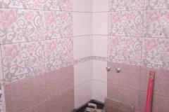 Укладка плитки на стены в ванной комнате новой квартиры.